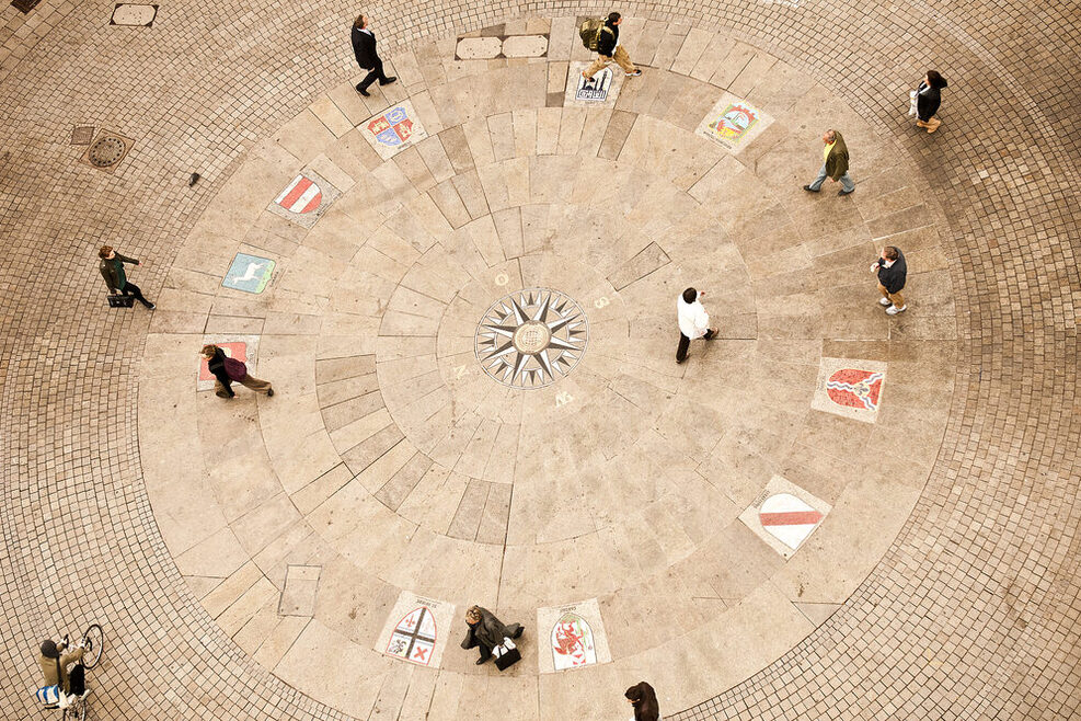 Several people walk across a square in which coats of arms are embedded in the ground.
